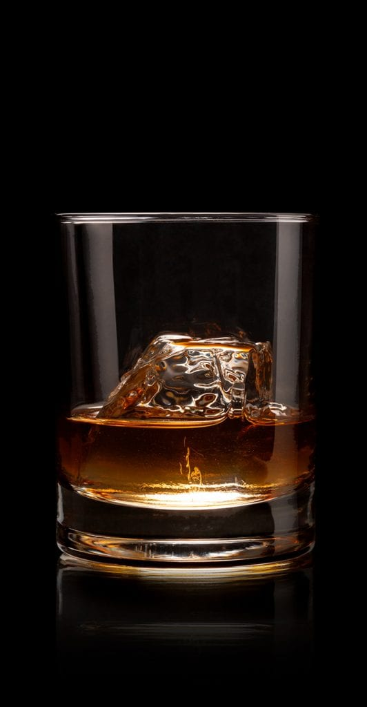 A glass of Five and 20 Spirits with ice dropping into glass with Reflection - Image Link